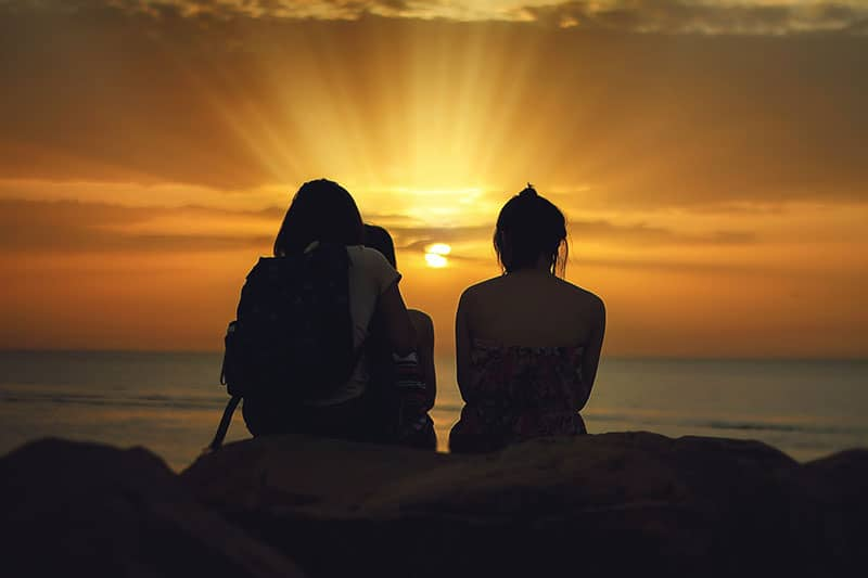 Geschwister sitzen im Sonnenuntergang am Meer