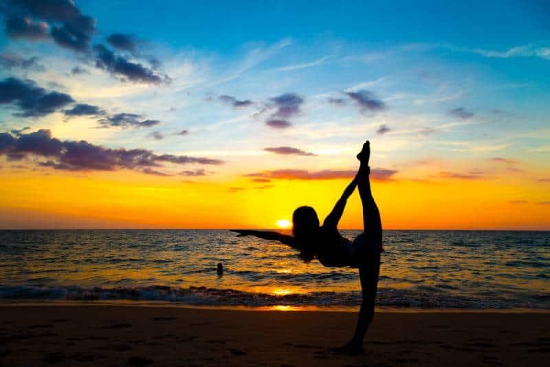 Gesunde Sportfrauen, die Yoga mit Meditation auf Strandsonnenuntergang tun