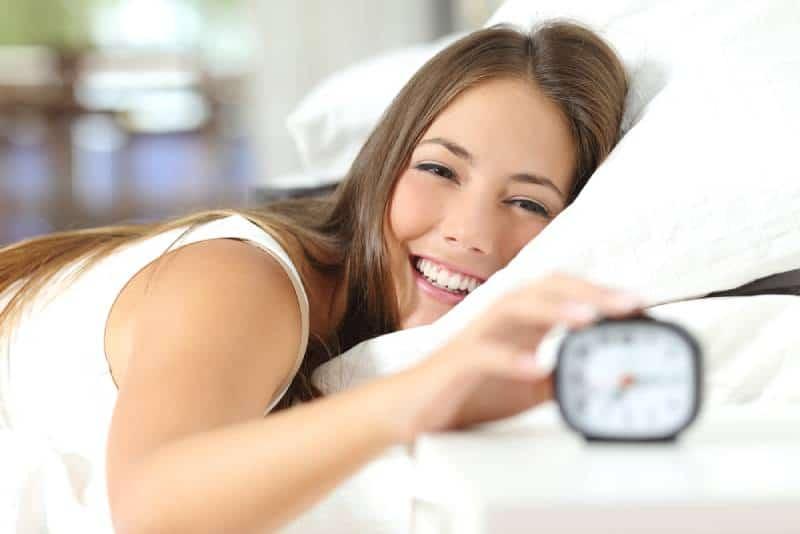 Glückliche Frau, die aufwacht und den Wecker ausschaltet, der einen guten Tag hat