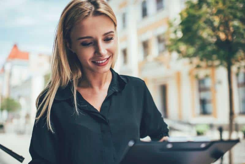 Glückliche Frau in der Freizeitkleidung, die Informationen von Papieren analysiert, die im Straßencafé sitzen