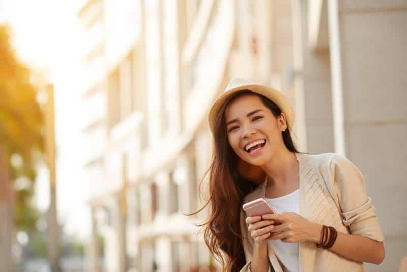 Glückliche Frau mit dem Smartphone, das in der Straße steht