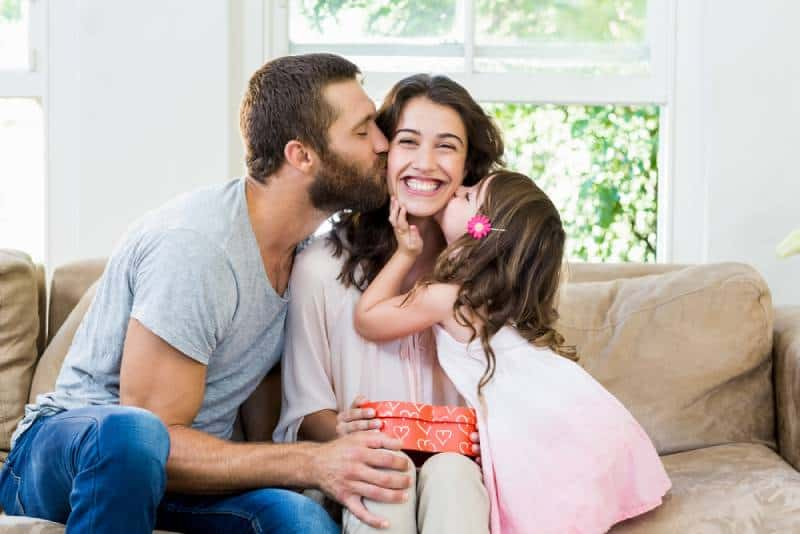 Glückliche Mutter, die ein Geschenk von ihrem Mann und ihrer Tochter im Wohnzimmer erhält