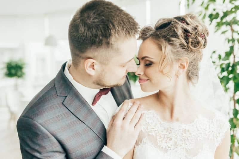 Glückliche schöne Jungvermählten, die im Restaurant umarmen