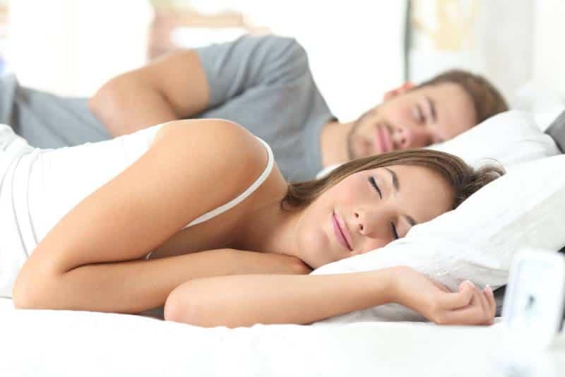 Glückliches Paar, das in einem bequemen Bett zu Hause schläft