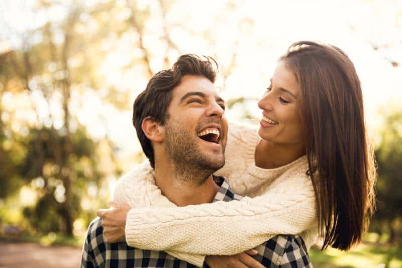 Glückliches Paar im Park, das einander ansieht und lacht