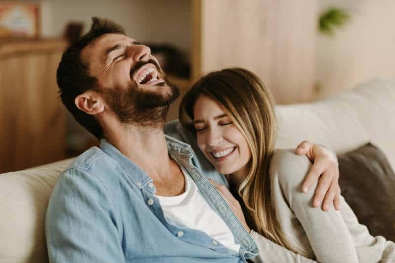 Glückliches junges Paar, das lacht, während es über etwas spricht