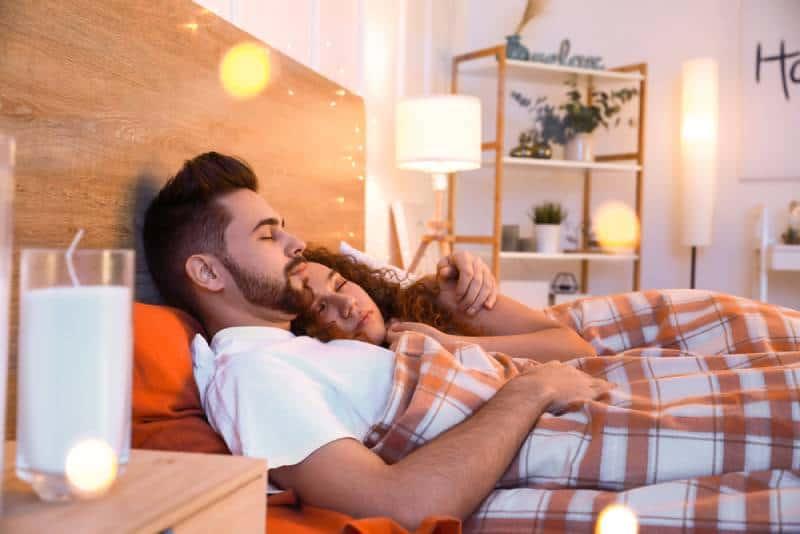 Glückliches junges Paar, das nachts im Bett schläft