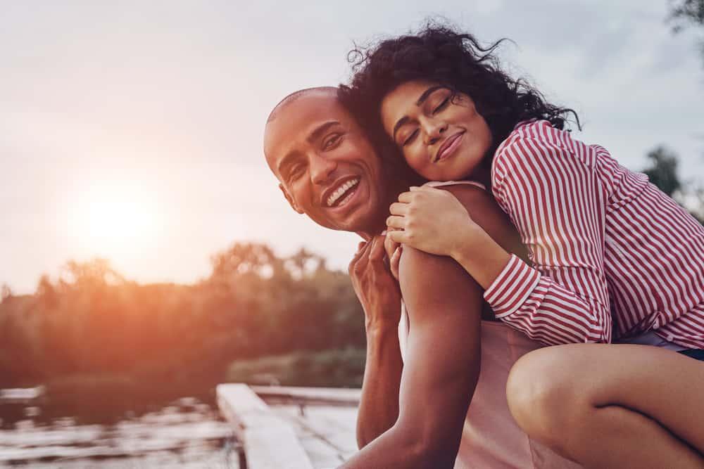 Glückliches junges Paar, das umarmt und lächelt, während es auf dem Pier nahe dem See sitzt