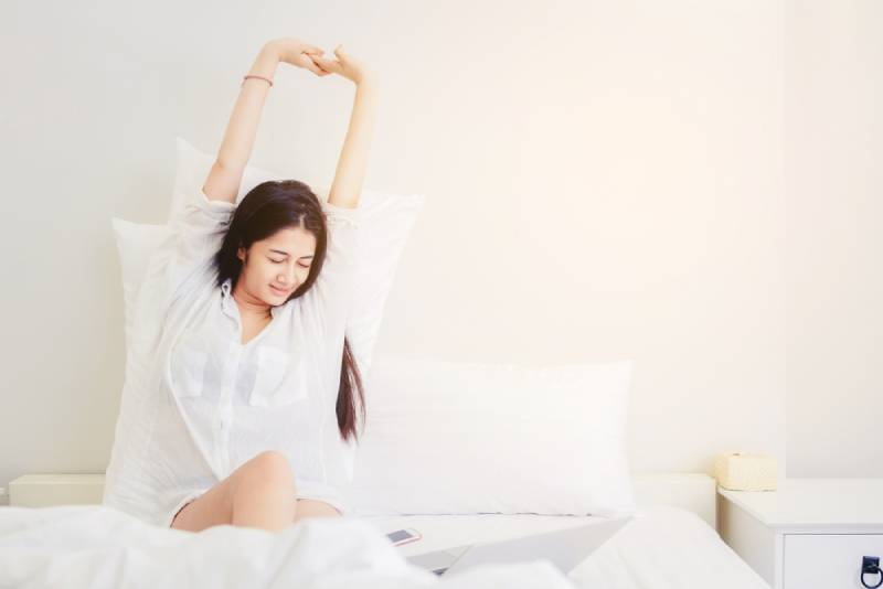Glücksfrau, die aufwacht und am Morgen mit einer Dehnung auf dem Bett gähnt