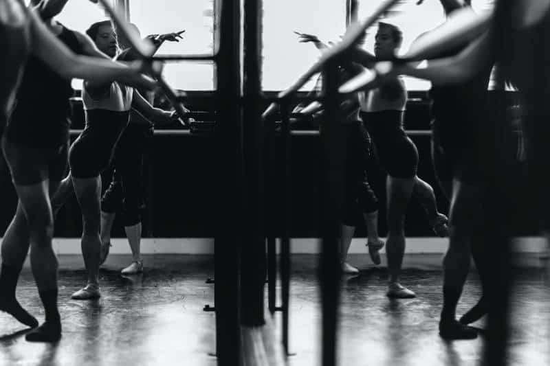 Graustufenfoto von Frauen, die vor dem Spiegel trainieren