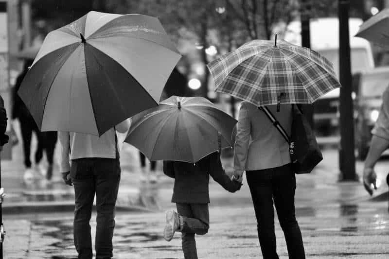 Graustufenfotografie von drei Personen mit Regenschirm