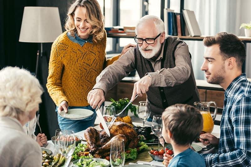 Großvater schneidet Truthahn mit Familie am Abendessen