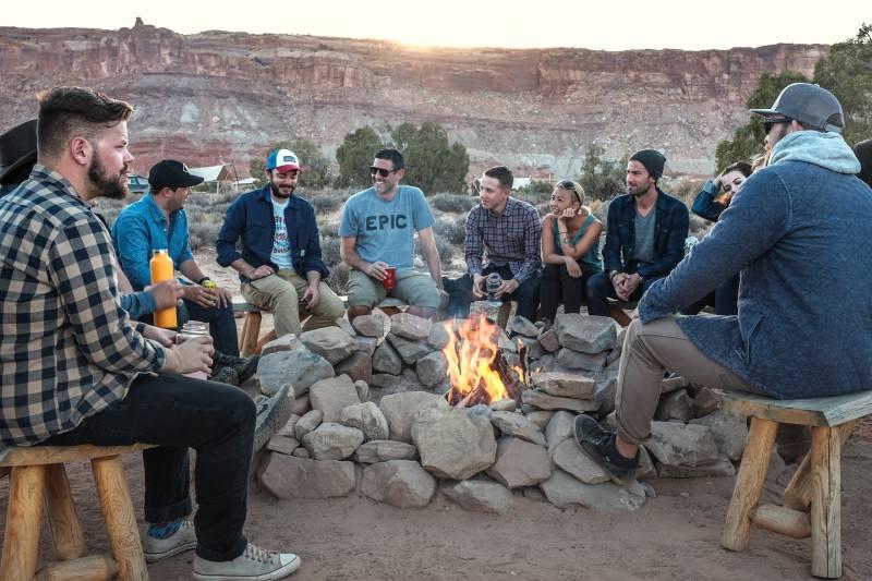 Gruppe von Freunden am Feuer sitzen und plaudern
