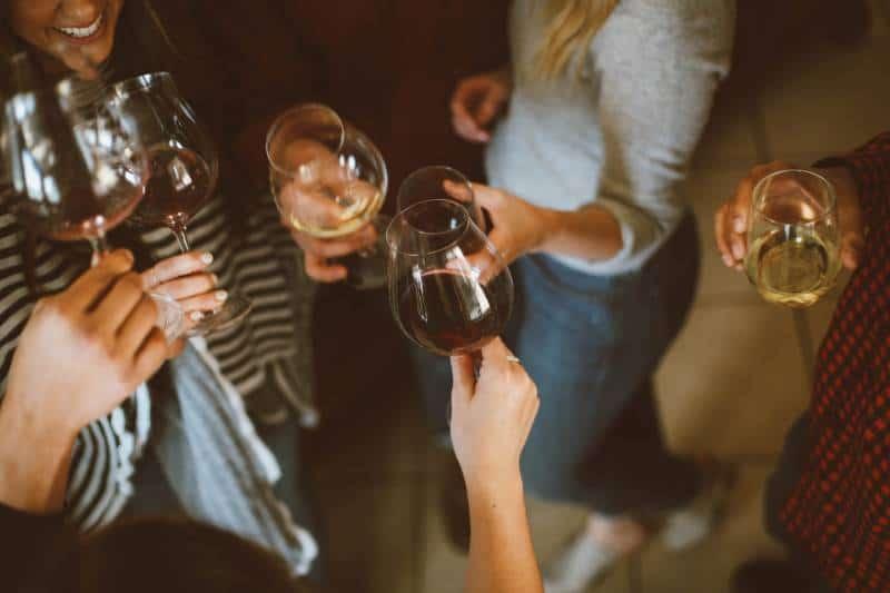 Gruppe von Freunden jubeln mit Gläsern Wein