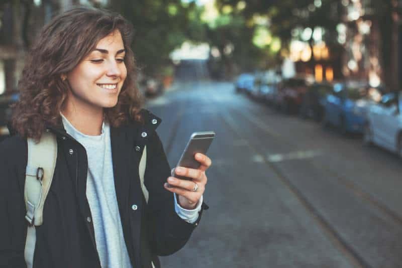 Hübsche lächelnde Frau mit Handy, das auf der Straße geht