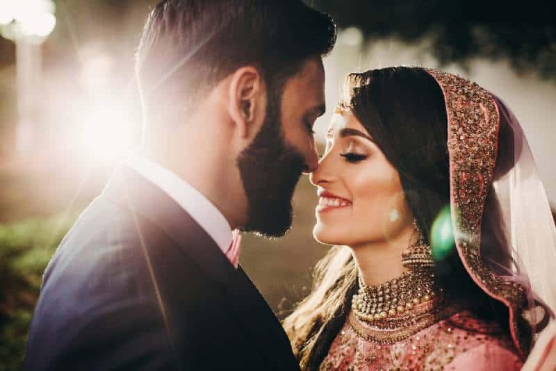 Hübscher bärtiger indischer Bräutigam küsst Braut im rosa Kleid