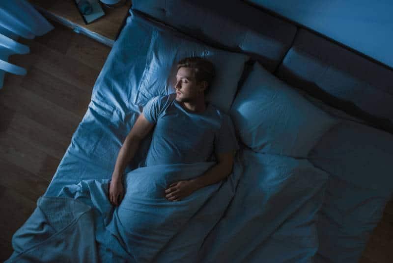 Hübscher junger Mann, der gemütlich auf einem Bett schläft