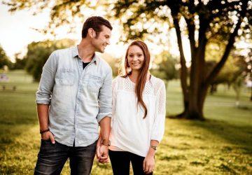 Mann, der Hand der Frau hält, die nahe Baum steht