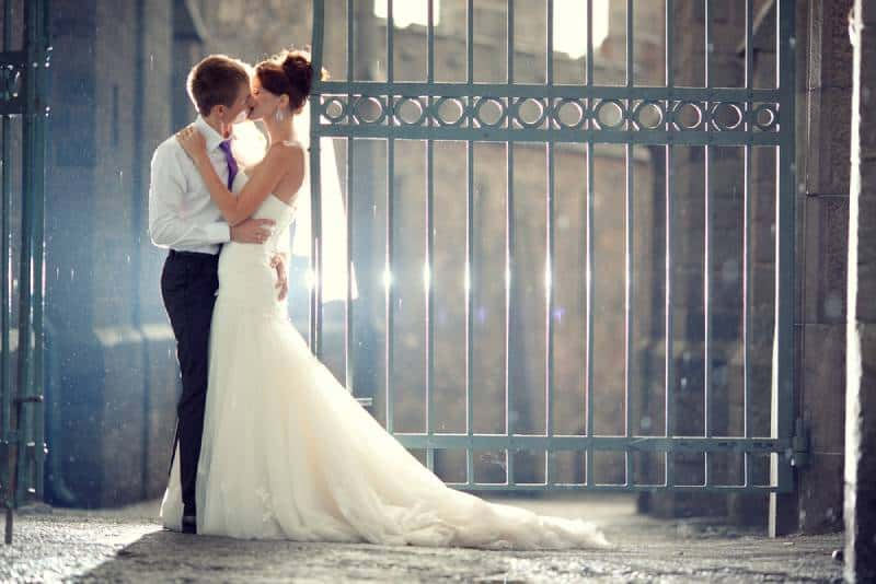 Hochzeitspaar Umarmungen und Küsse am Tor