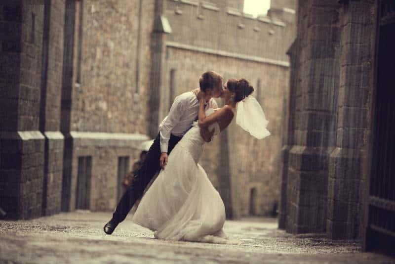 Hochzeitspaar umarmt und küsst sich am Tor