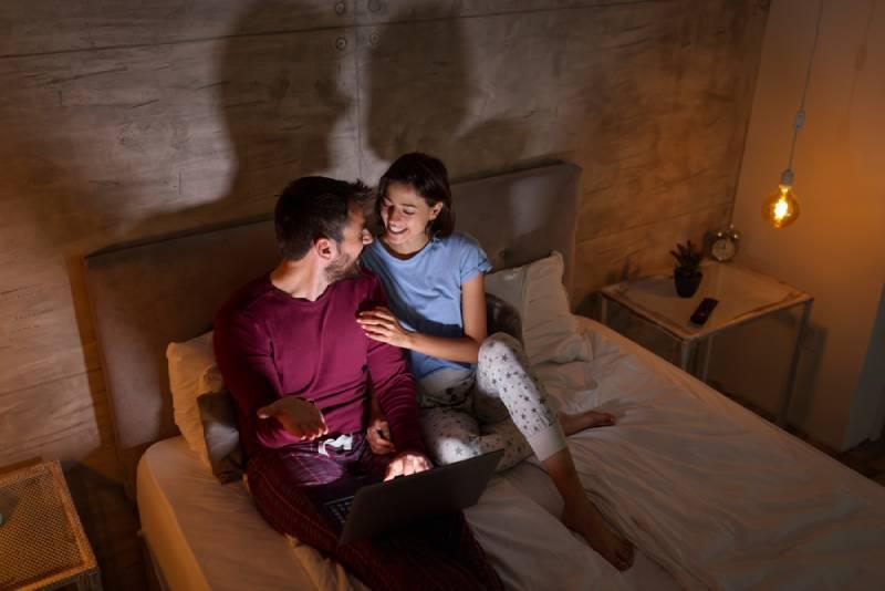 Hohe Winkelansicht des schönen Paares, das nachts im Bett liegt,