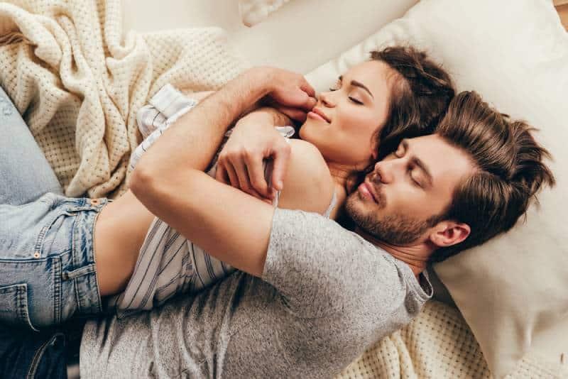 Hohe Winkelansicht des schönen glücklichen jungen Paares, das beim Schlafen auf dem Bett umarmt