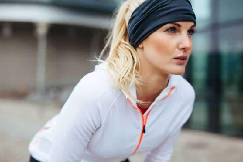 Junge Frau, die sich in Sportausrüstung beugt