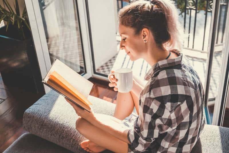 Junge hübsche Frau, die am geöffneten Fenster sitzt und Kaffee trinkt