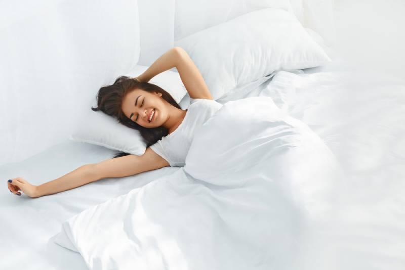 Junge schöne Frau, die in ihrem Bett völlig ausgeruht aufwacht.