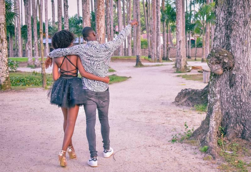 Junges Paar, das im Park mit zeigendem Kerl geht