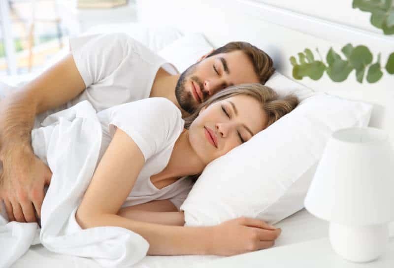 Junges süßes Paar, das zusammen im Bett schläft