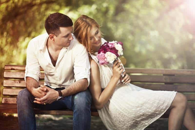 Junges schönes Paar, das im Park sitzt und Mann Frau vorschlägt.
