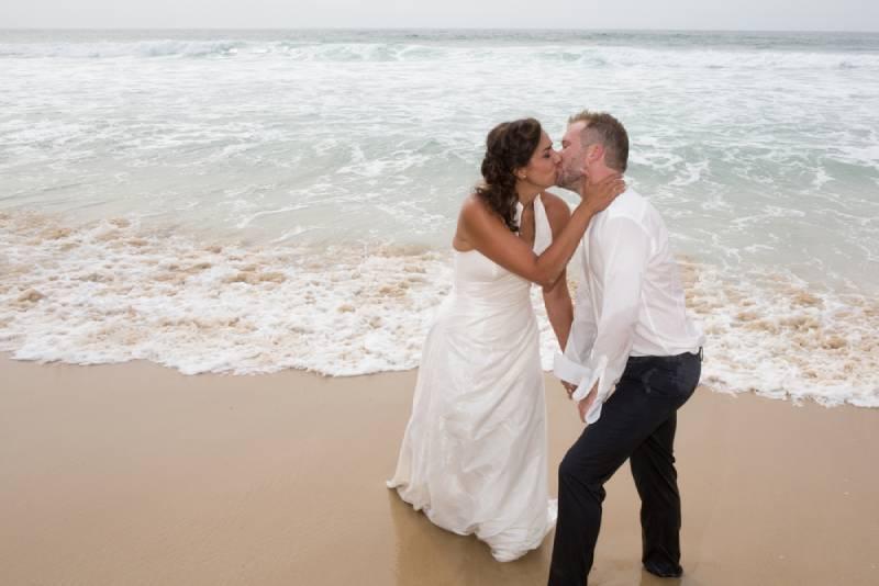 Jungvermählten teilen einen romantischen Moment am Strand und küssen sich
