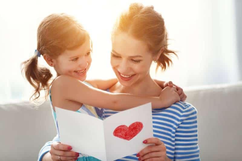 Kind Tochter gratuliert Müttern und gibt ihr eine Postkarte