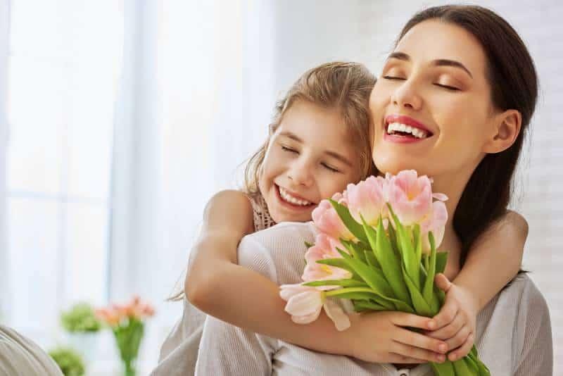 Kind Tochter gratuliert Mutter und gibt ihren Blumen Tulpen.