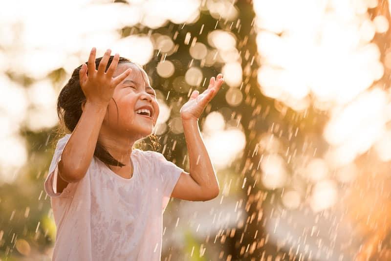 glückliches asiatisches Mädchen, das auf Regen steht