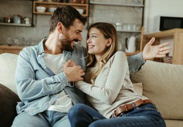 glückliches Paar, das auf Sofa kuschelt