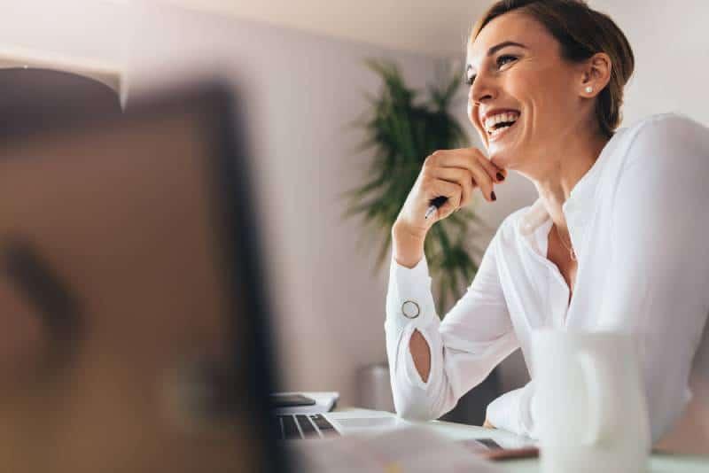 Lächelnde Frau, die an ihrem Schreibtisch im Büro sitzt