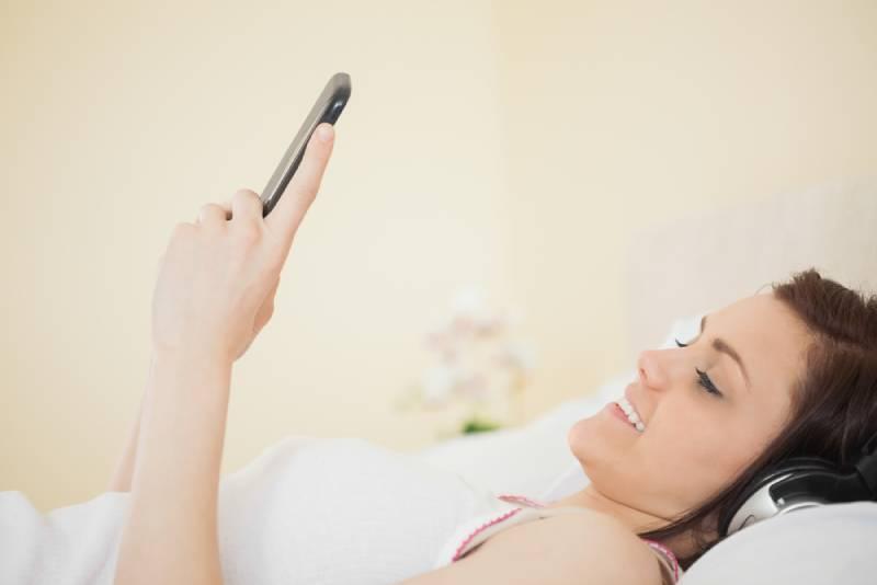 Lächelndes Mädchen, das Musik auf ihrem Smartphone hört, das auf Bett in einem Schlafzimmer liegt