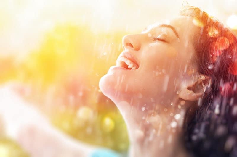 glückliche Frau, die auf Regen lächelt