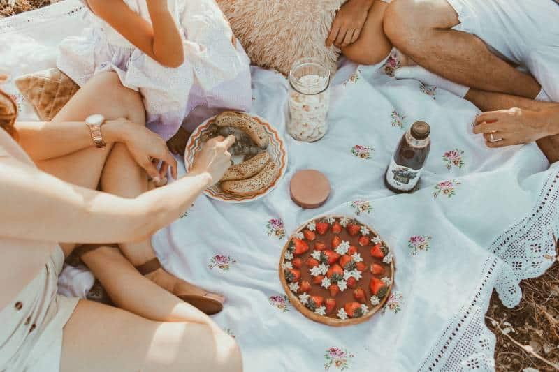 Leute, die auf weißem Textil sitzen, das Brot nahe Kuchen isst