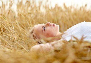 blonde Frau, die auf dem Feld liegt