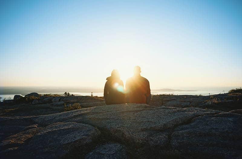 Paar sitzt auf Stein draußen in der Natur