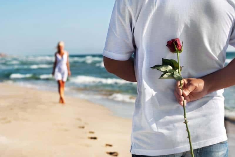 Liebespaar - Mann mit Rose wartet auf seine Frau am Meeresstrand