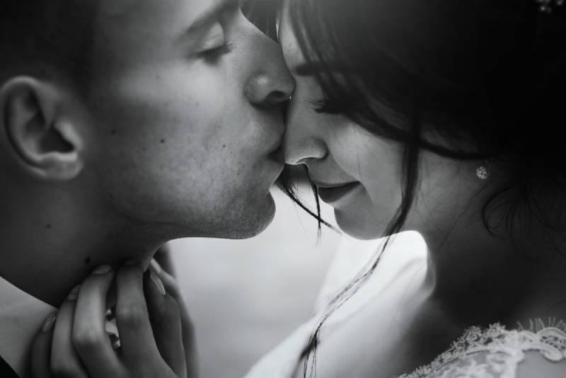 Luxus-Hochzeitspaar, das das Umarmen und Küssen im sonnigen Licht umarmt