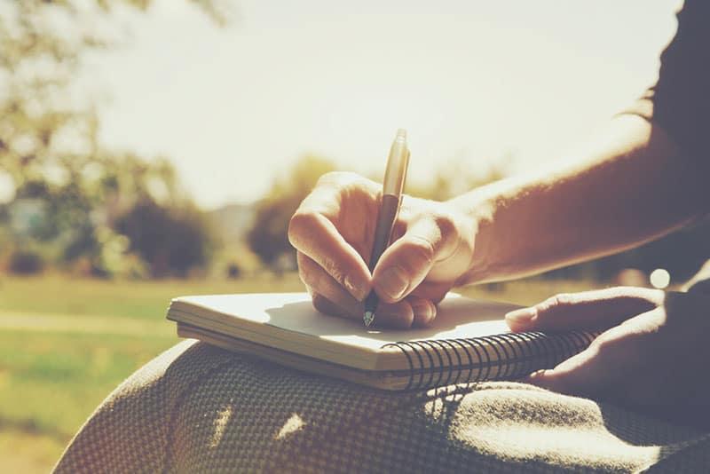 Mädchen Hand auf dem Notizbuch