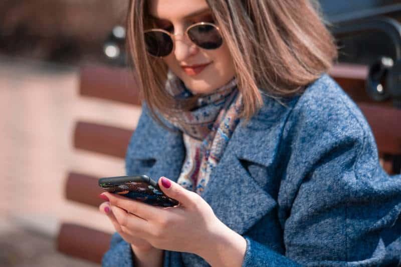 Mädchen, das auf ihrem Telefon tippt, während es auf Parkbank sitzt