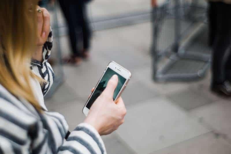Mädchen, das draußen ein Telefon tippt