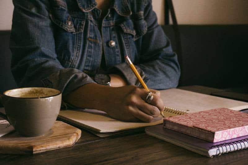 Mädchen, das in Notizbuch zu Hause schreibt