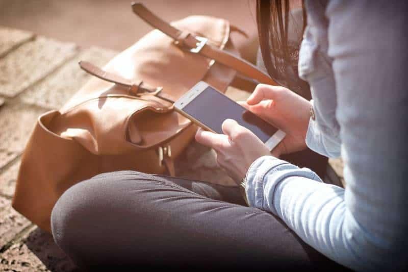 Mädchen sitzt auf Ziegeln und tippt eine SMS